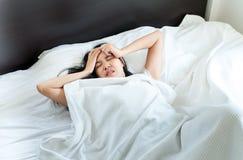 Den asiatiska kvinnan har en huvudvärk på säng efter vak upp i morgonen royaltyfria foton