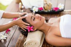 Den asiatiska kvinnan i brunnsortsalongen, masserar huvudet Royaltyfri Foto