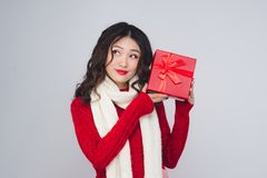 Den asiatiska kvinnan i rött värme kläder med gåvan Nytt år för ferier och royaltyfri foto