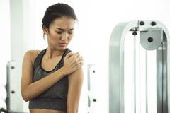 Den asiatiska kvinnan i sportswearen som har skuldran, smärtar royaltyfri foto