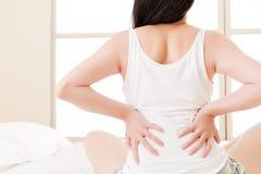 Den asiatiska kvinnan lider smärtar tillbaka ryggvärken, ryggrads- lägre problem Fotografering för Bildbyråer