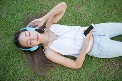 Den asiatiska kvinnan lyssnar musik på gräs arkivbilder