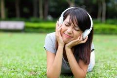Den asiatiska kvinnan lyssnar till sången Royaltyfria Bilder