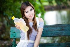 Den asiatiska kvinnan med en buteljera av bevattnar i parkera Arkivfoton