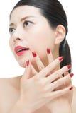 Den asiatiska kvinnan med rött mode spikar polermedel och sinnliga kanter Arkivfoto