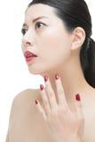 Den asiatiska kvinnan med rött mode spikar polermedel och sinnliga kanter Royaltyfri Bild