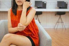 Den asiatiska kvinnan med smärtar på armbågen, den kvinnliga handen som trycker på hennes smärtsamma arm och armbågar arkivfoton