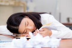 Den asiatiska kvinnan med trött överansträngt och sömn, flicka har att vila, medan arbetshandstilanmärkningen, Arkivbild