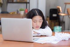 Den asiatiska kvinnan med trött överansträngt och sömn, flicka har att vila, medan arbetshandstilanmärkningen, royaltyfri bild