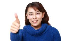 den asiatiska kvinnan med tummar gör en gest upp Royaltyfria Bilder