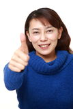 den asiatiska kvinnan med tummar gör en gest upp Royaltyfri Foto