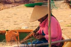 Den asiatiska kvinnan sitter i runt fartyg och väver fisknät Arkivfoto