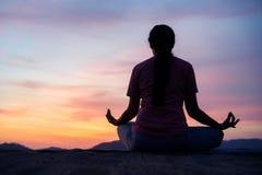 Den asiatiska kvinnan sitter lotusblommayogaposition på solnedgången ?vande yoga g?r meditationen f?r sunt andas och avkoppling royaltyfri fotografi