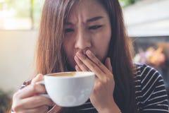 Den asiatiska kvinnan sitter med hakan som vilar på hennes händer och stänger henne ögon som luktar varmt kaffe på trätabellen me fotografering för bildbyråer