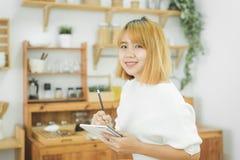 Den asiatiska kvinnan skriver shoppinglistor i notepad vid pennan på hennes diskbänk hemma arkivbild