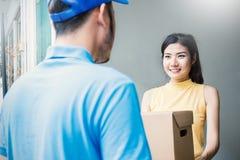 Den asiatiska kvinnan som accepterar, mottar en leverans av askar från leveransasiatman Royaltyfri Fotografi