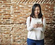 Den asiatiska kvinnan som använder mobil, ringer Fotografering för Bildbyråer