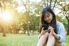 Den asiatiska kvinnan som använder på den smarta telefonen med känsla, kopplar av och smileyframsidan fotografering för bildbyråer