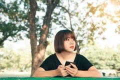 Den asiatiska kvinnan som använder på den smarta telefonen med känsla, kopplar av och smileyframsidan Livsstil- och teknologibegr arkivbild