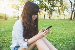 Den asiatiska kvinnan som använder på den smarta telefonen med känsla, kopplar av och smileyframsidan Livsstil- och teknologibegr royaltyfri foto