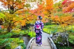 Den asiatiska kvinnan som bär den japanska traditionella kimonot i höst, parkerar japan Arkivbilder