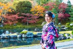 Den asiatiska kvinnan som bär den japanska traditionella kimonot i höst, parkerar japan Royaltyfri Fotografi