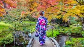 Den asiatiska kvinnan som bär den japanska traditionella kimonot i höst, parkerar Kyoto i Japan arkivfoton