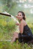 Den asiatiska kvinnan som bär traditionell thai kultur, tar en baht på duri Royaltyfria Foton