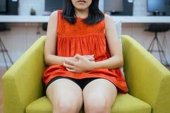 Den asiatiska kvinnan som har smärtsamt magknip hemma, kvinnligt lidande från buk-, smärtar, periodkramper, händer som pressar bu arkivfoton