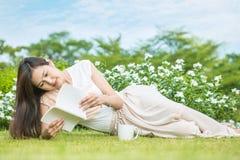 Den asiatiska kvinnan som ligger på gräsfältet för, läste en vit bok i parkera, avkopplingbegrepp av den härliga asiatiska kvinna Arkivbilder