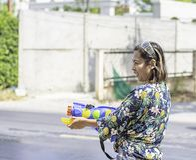 Den asiatiska kvinnan som rymmer ett vattenvapen, spelar den Songkran festivalen eller thailändskt nytt år i Thailand royaltyfri fotografi