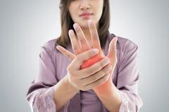 Den asiatiska kvinnan som rymmer hennes hand mot grå bakgrund, smärtar conc royaltyfri foto