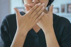 Den asiatiska kvinnan som täcker hennes mun och, luktar hennes andedräkt med handuptervaken upp, den dåliga lukten fotografering för bildbyråer