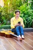 Den asiatiska kvinnan tycker om att bläddra internet på den smarta telefonen royaltyfri bild