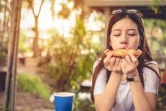 Den asiatiska kvinnan tycker om att ?ta skivan av pizza p? utomhus Lycka efter bantar begrepp Folklivsstil och italienarematbegre royaltyfri bild