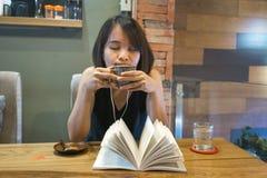 Den asiatiska kvinnan tycker om fri tid med boken, kaffe och musik royaltyfri foto