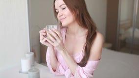 Den asiatiska kvinnan vaknade precis upp och dricka något vatten för hälsa bredvid fönstret stock video