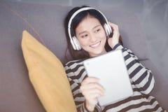 Den asiatiska kvinnan vilar som lyssnar till musik på soffan med hörluren arkivbild