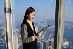 Den asiatiska kvinnliga chefen använder den digitala minnestavlan för sökande av nödvändig information fotografering för bildbyråer