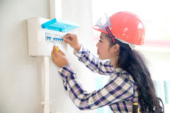 Den asiatiska kvinnliga elektriker- eller teknikerkontrollen eller kontrollerar säkerhetsbrytaren för strömkretsen för det elektr royaltyfria bilder