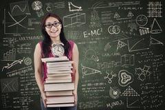 Den asiatiska kvinnliga studenten kommer med bunten av böcker i grupp Arkivbild