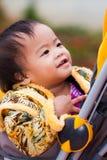 Den asiatiska kvinnlign behandla som ett barn leende i perambulator Arkivbilder
