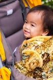Den asiatiska kvinnlign behandla som ett barn leende i perambulator Royaltyfri Bild