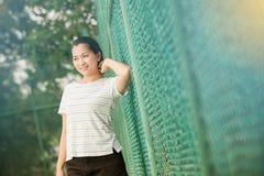 Den asiatiska kvinnlign kopplar av och ler anseende på tennisbanan Royaltyfri Foto