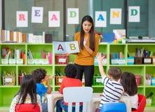Den asiatiska lärarinnan som undervisar och frågar ungar för blandat lopp, räcker upp royaltyfria bilder