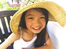Den asiatiska långa flickan för svart hår bär sugrörhatten Hon sitter arkivbild