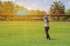 Den asiatiska långa hårkvinnagolfaren slogg golf i grön golfförbannelse arkivbild
