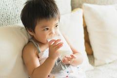 Den asiatiska lilla flickan är rymma, och dricka ett exponeringsglas av mjölka i liv arkivfoto