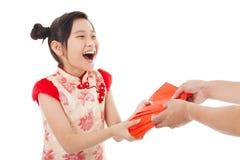 Den asiatiska lilla flickan mottog det röda kuvertet arkivbild