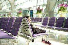 Den asiatiska lilla flickan sitter på stolen i väntan för flygplatsterminalen royaltyfri foto